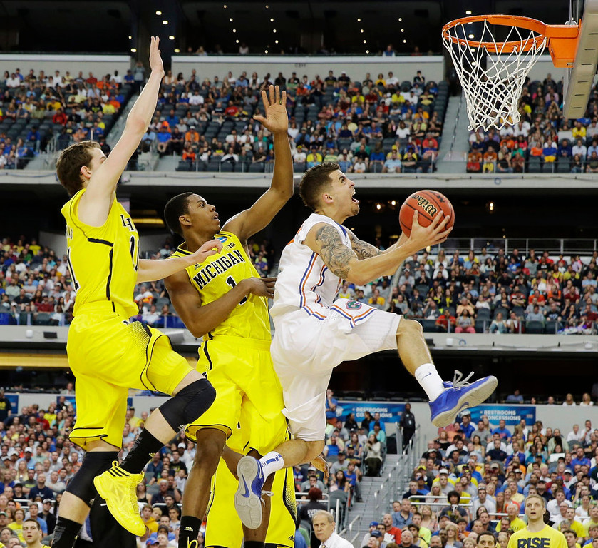 . Florida\'s Scottie Wilbekin (5) shoots as Michigan\'s Glenn Robinson III (1) and Nik Stauskas (11) defend during the first half of a regional final game in the NCAA college basketball tournament, Sunday, March 31, 2013, in Arlington, Texas. (AP Photo/David J. Phillip)