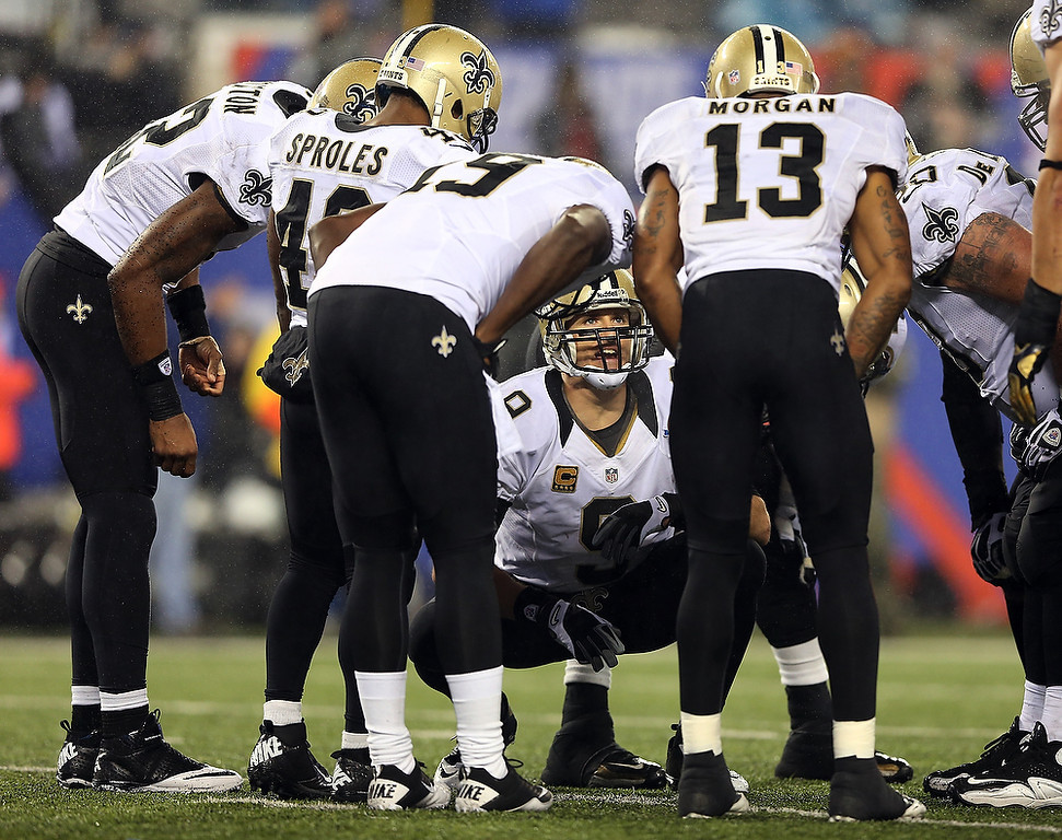 . Drew Brees #9 of the New Orleans Saints talks in the huddle during the fourth quarter against the New York Giants on December 9, 2012 at MetLife Stadium in East Rutherford, New Jersey.  (Photo by Elsa/Getty Images)