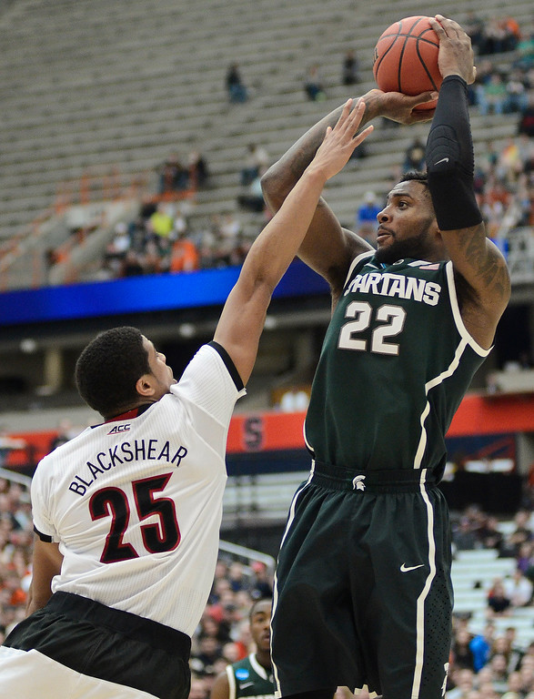 . Michigan State\'s Branden Dawson (22) shoots over Louisville\'s Wayne Blackshear (25) during the second half of a regional final in the NCAA men\'s college basketball tournament Sunday, March 29, 2015, in Syracuse, N.Y.  (AP Photo/Heather Ainsworth)