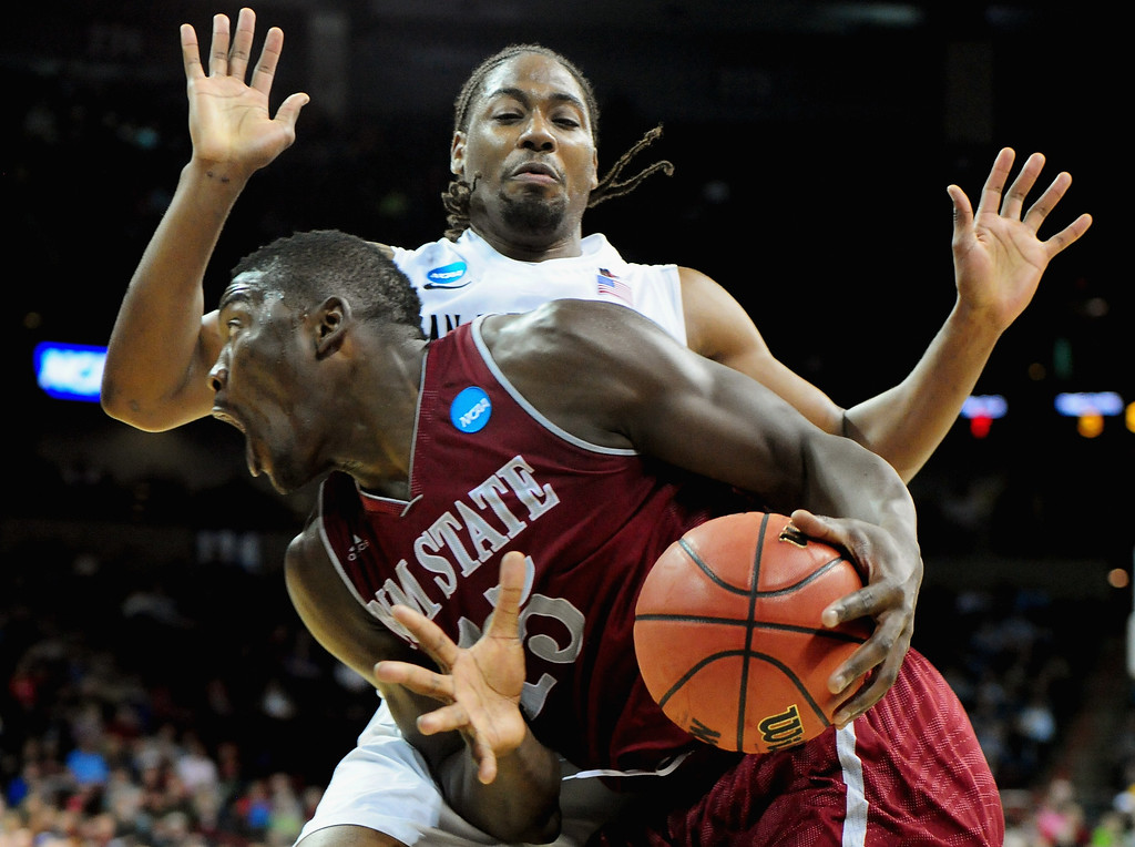 . Tshilidzi Nephawe #15 of the New Mexico State Aggies drives the ball around Josh Davis #22 of the San Diego State Aztecs during the second round of the 2014 NCAA Men\'s Basketball Tournament at Spokane Veterans Memorial Arena on March 20, 2014 in Spokane, Washington.  (Photo by Steve Dykes/Getty Images)