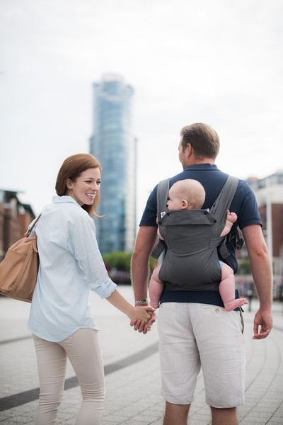 Izmi_Baby_Carrier_Mid_Grey_Lifestyle_Back_Carry_Mum_And_Dad_Walking_In_City.jpg