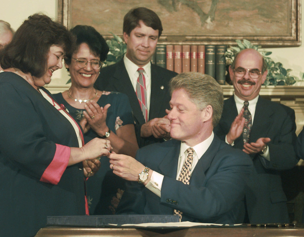 . President Clinton presents a pen to Jeanne White, mother of Ryan White,  after signing the Ryan White Re-authorization Act at the White House, Monday, May 20, 1996. Applauding the presentation are, second from left, AIDS Director Patsy Flemming, Sen. Bill Frist, R-Tenn. and Rep. Henry Waxman, D-Calif.  (AP Photo/Greg Gibson)