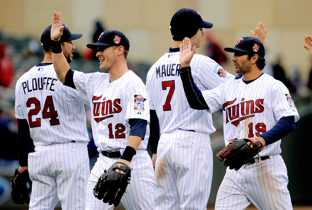 . Minnesota Twins\' Trevor Plouffe (24), Chris Herrmann (12), Joe Mauer (7) and Darin Mastroianni (19) celebrate the Twins\' 4-3 win over the Kansas City Royals in a baseball game in Minneapolis, Sunday, April 13, 2014. (AP Photo/Tom Olmscheid)
