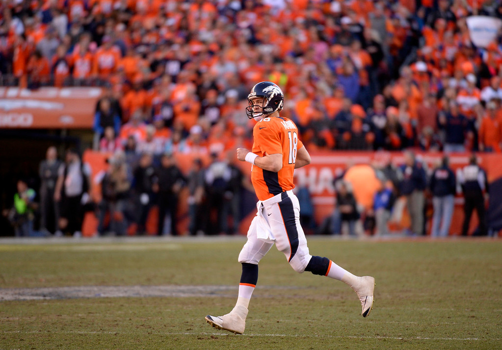 . Denver Broncos quarterback Peyton Manning (18) runs onto the field during the fourth quarter. The Denver Broncos vs. The New England Patriots in an AFC Championship game  at Sports Authority Field at Mile High in Denver on January 19, 2014. (Photo by John Leyba/The Denver Post)