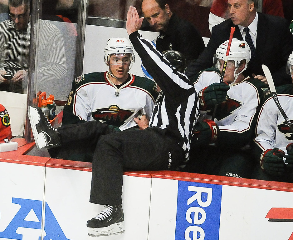 . A referee calls off sides after being hit in to the Wild bench in the first period. (Pioneer Press: Ben Garvin)
