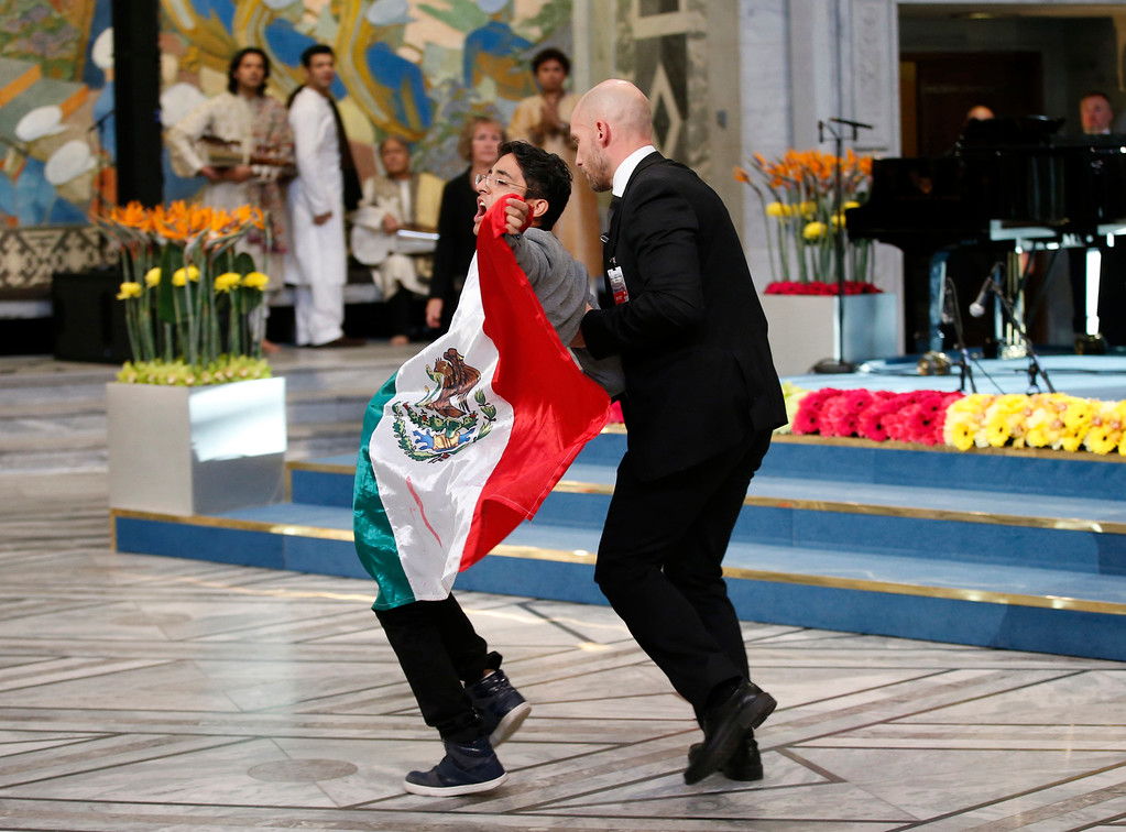 . A man holding the Mexican flag is led away by security after attempting to get on stage with Nobel Peace Prize winners Malala Yousafzai from Pakistan and Kailash Satyarthi of India during the Nobel Peace Prize award ceremony in Oslo, Norway, Wednesday, Dec. 10, 2014.  The Nobel Peace Prize is being shared between Malala Yousafzai, the 17-year-old Taliban attack survivor, and the youngest Nobel Prize winner ever, and Indian children\'s rights activist Kailash Satyarthi in a ceremony in Oslo on Wednesday.  (AP Photo/Cornelius Poppe, Scanpix)