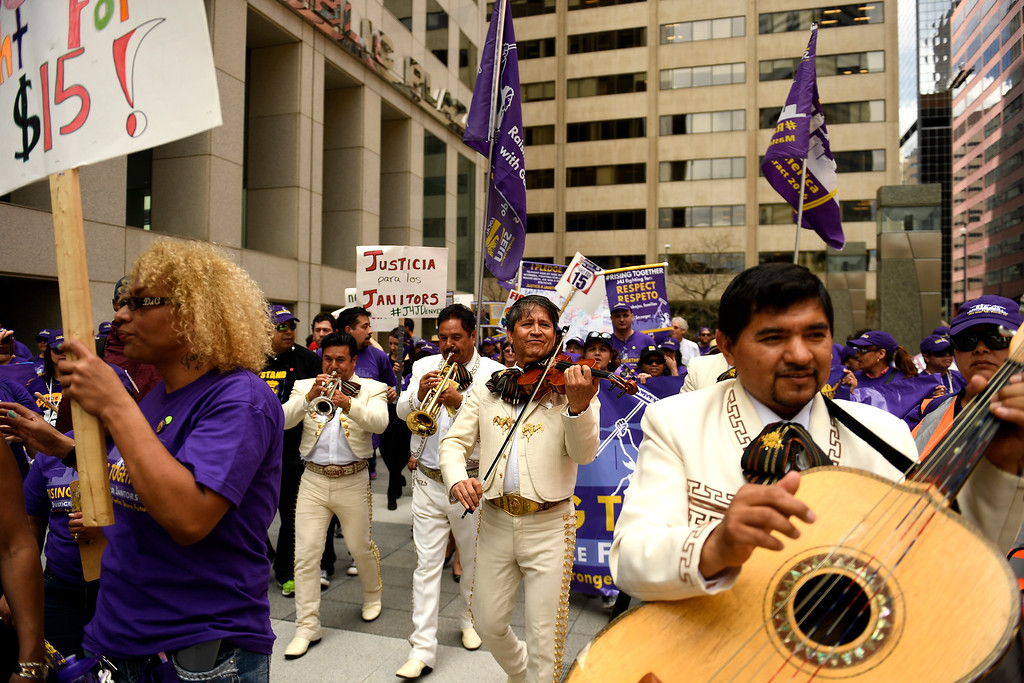 . Denver, CO - ARRIL 14: Mariachi Musicians march and play with the low wage janitors as they kicked off their contract campaign with a rally at Civic Center Park�s Veterans Memorial in downtown and a march past all the buildings where they do their work in Denver. The janitors were joined by local care workers, Fast food, delivery persons and service workers during their  Underpaid Fight for $15 march. April 14, 2016 in Denver, CO. (Photo By Joe Amon/The Denver Post)