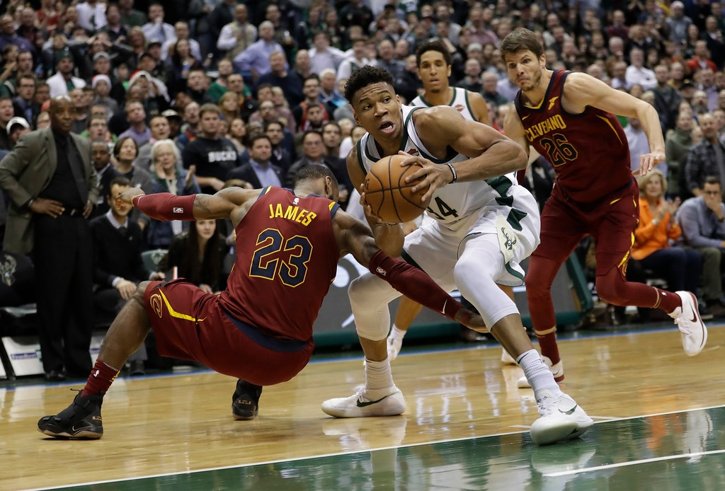 . Milwaukee Bucks\' Giannis Antetokounmpo gabs a loose ball in front of Cleveland Cavaliers\' LeBron James during the second half of an NBA basketball game Tuesday, Dec. 19, 2017, in Milwaukee. The Bucks won 119-116. (AP Photo/Morry Gash)