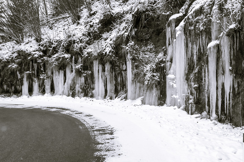 Stalactites growing beside a mountain road in winter.