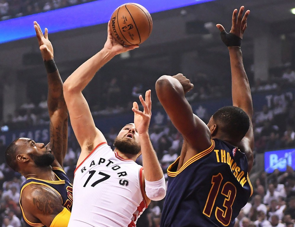 . Toronto Raptors center Jonas Valanciunas (17) shoots between Cleveland Cavaliers forward LeBron James, left, and center Tristan Thompson (13) during the first half of Game 3 of an NBA basketball second-round playoff series in Toronto on Friday, May 5, 2017. (Frank Gunn/The Canadian Press via AP)