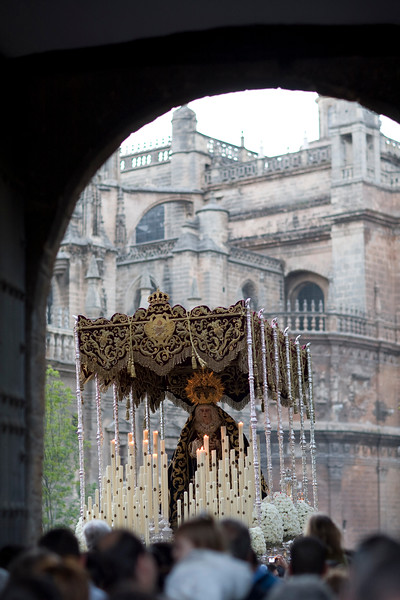 Framed view of a Holy Week float with the Virgin image in front of Seville's Cathedral, Spain