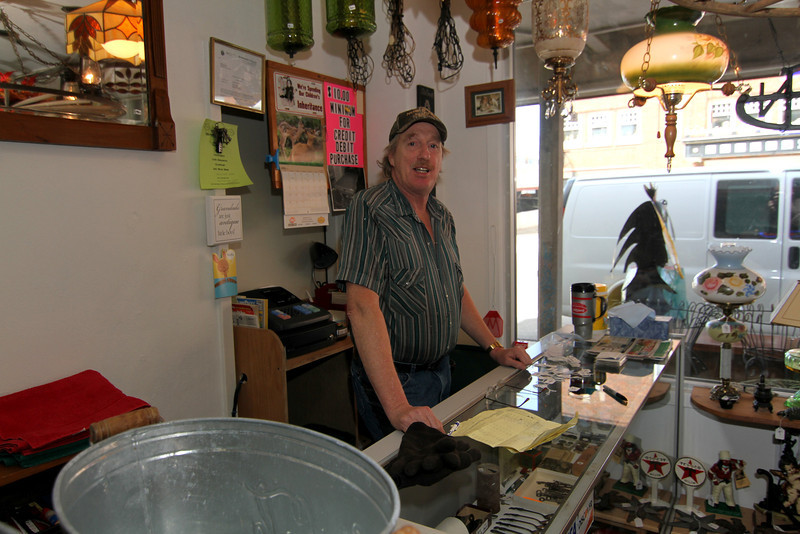 Dennis Foley behind the counter of Antiques & Collectibles