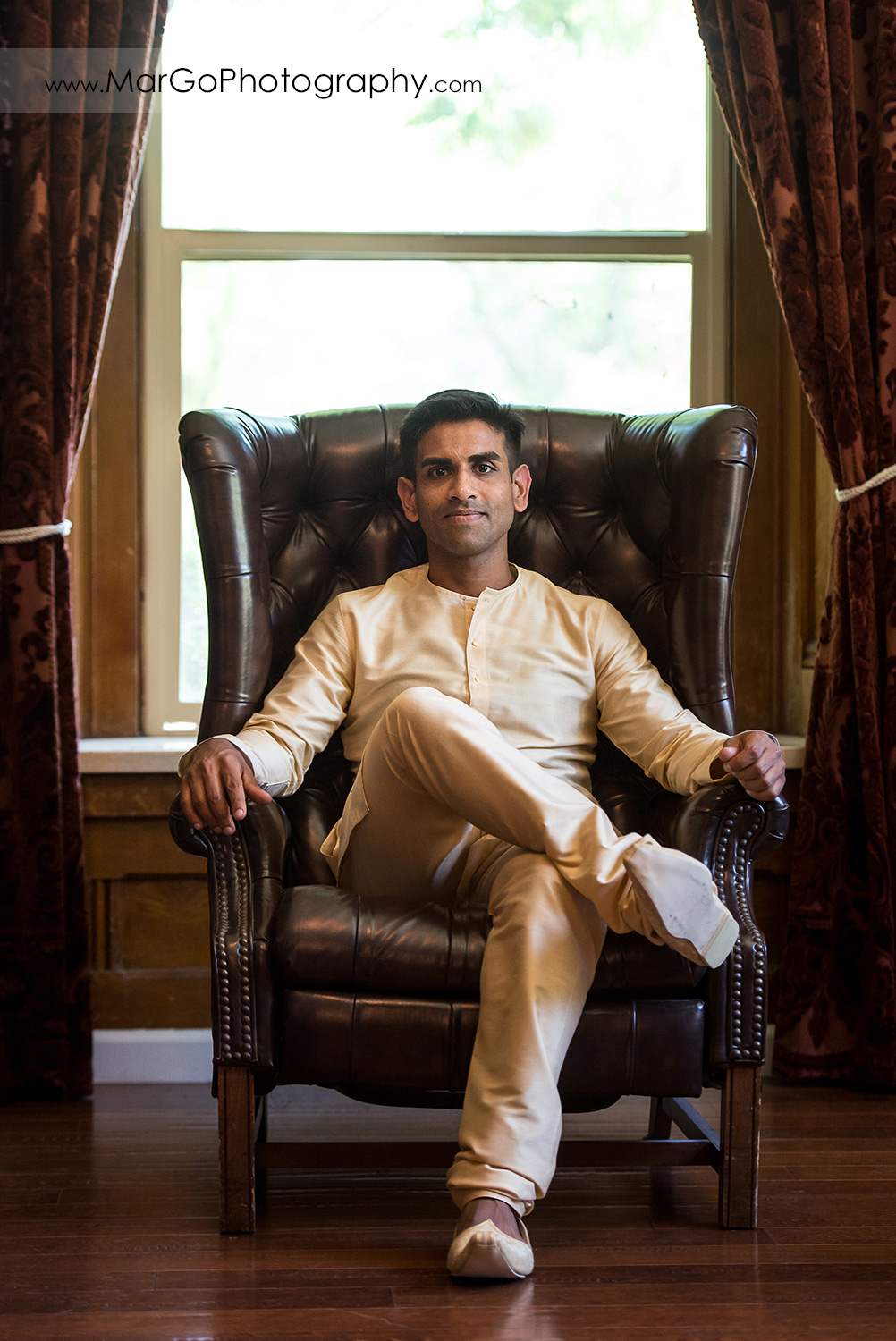 Indian groom sitting on leather chair at Elliston Vineyards in Sunol