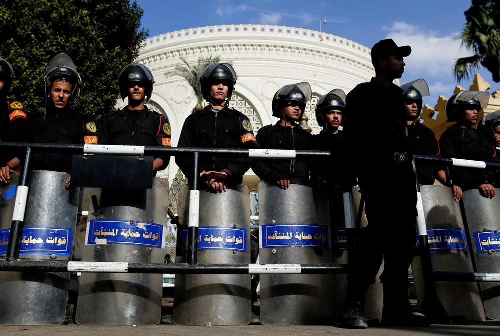 "Description of . Egyptian riot policemen guard a gate of the presidential palace, background, amid ongoing protests, in Cairo, Egypt, Saturday, Dec. 8, 2012. Egypt\'s military has warned of \'disastrous consequences\' if the political crisis gripping the country is not resolved through dialogue. "" (AP Photo/Hassan Ammar)"