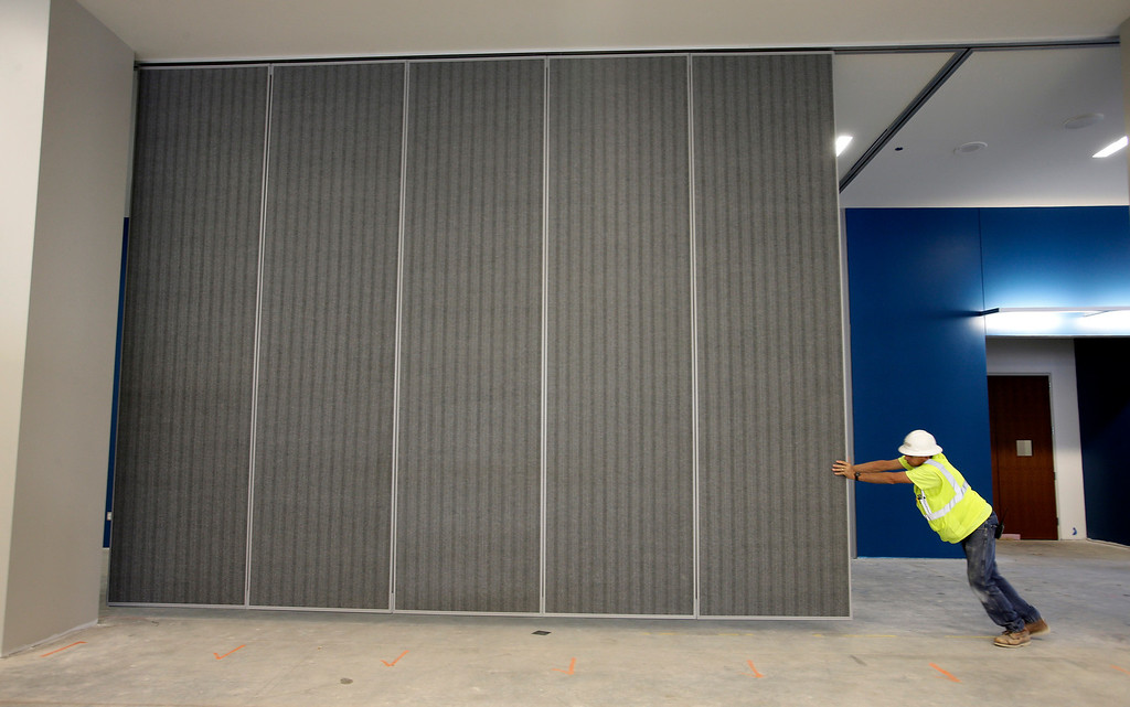 . Bill Bording places a portable wall into position in the meeting area of the new 125,000-square foot expansion of the San Jose McEnery Convention Center in San Jose, Calif. on Tuesday, Aug. 6, 2013.  (Gary Reyes/Bay Area News Group)