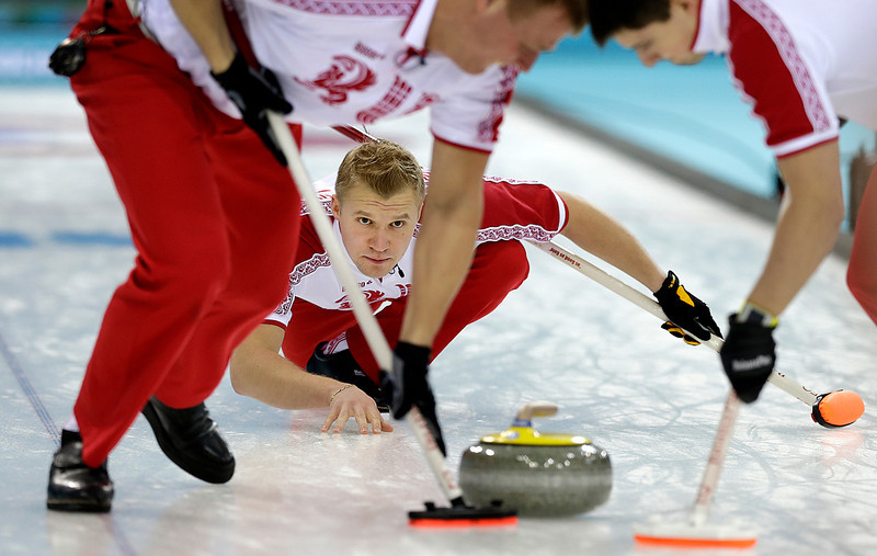 . Russia\'s Alexei Stukalskiy watches the rock while his teammates Andry Drozdov, left Anexander Kozyrev, right, sweep the ice  during the men\'s curling competition at the 2014 Winter Olympics, Tuesday, Feb. 11, 2014, in Sochi, Russia. (AP Photo/Wong Maye-E)