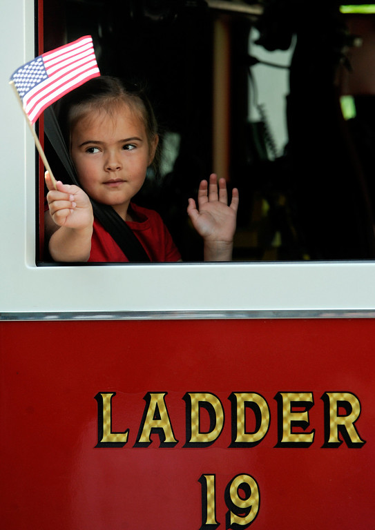. Gracie Kitka, 5, waves her flag and hand while riding in the Friendship Fire Companyís Ladder 19 in the Danville Memorial Day Parade, Monday, May 26, 2014, in  Danville, Pa. (AP Photo/Bloomsburg Press Enterprise, Jimmy May)