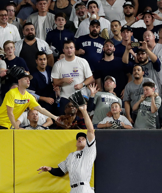 . New York Yankees right fielder Aaron Judge makes a catch at the wall on a line drive hit by Cleveland Indians\' Francisco Lindor during the sixth inning in Game 3 of baseball\'s American League Division Series, Sunday, Oct. 8, 2017, in New York. (AP Photo/Frank Franklin II)
