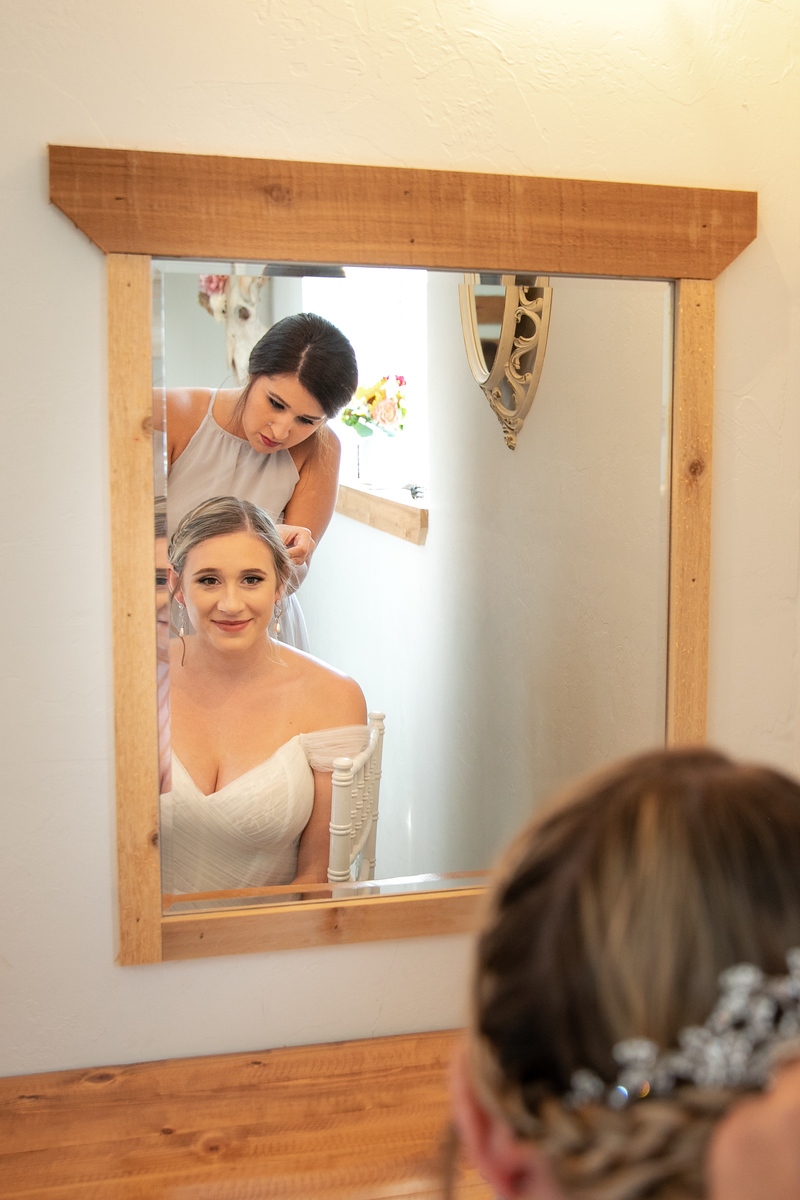 a bride looking in the mirror as a hairdresser puts finishing touches to her hair