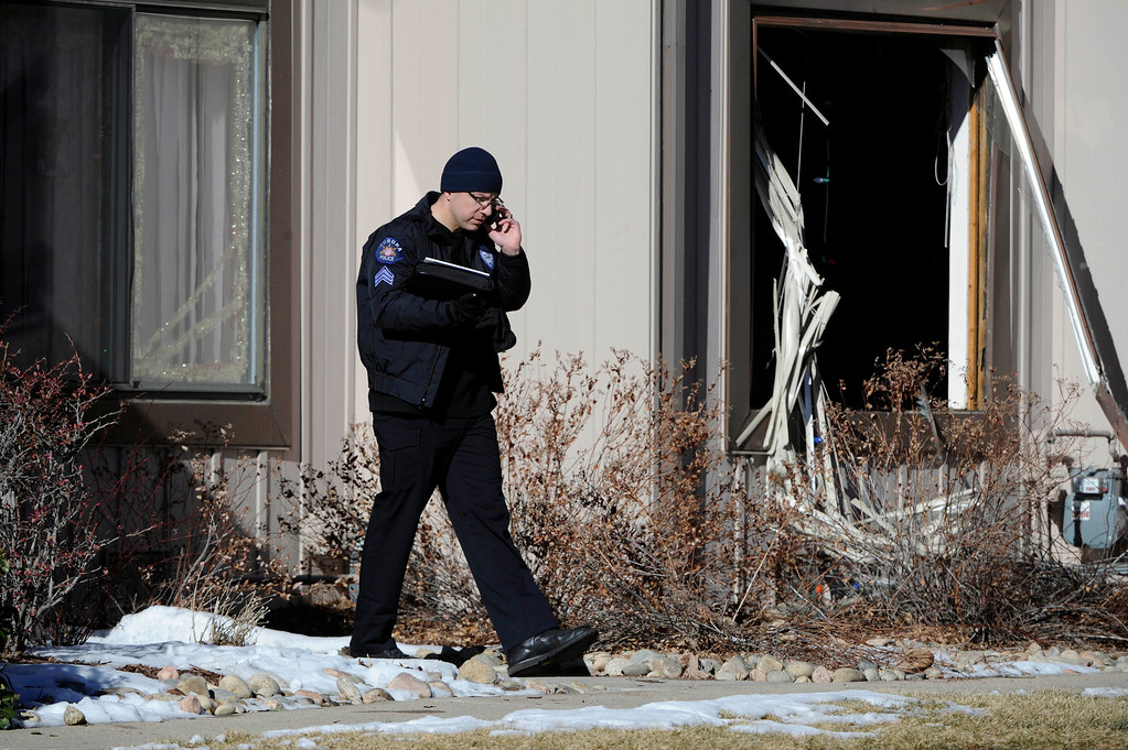 . An Aurora Police officer comes out of a town home next to a crime scene at 16005 Ithaca Place in Aurora Saturday afternoon. The bodies of four people, including a gunman are dead at the scene following a standoff situation early Saturday morning. The Denver Post/ Andy Cross
