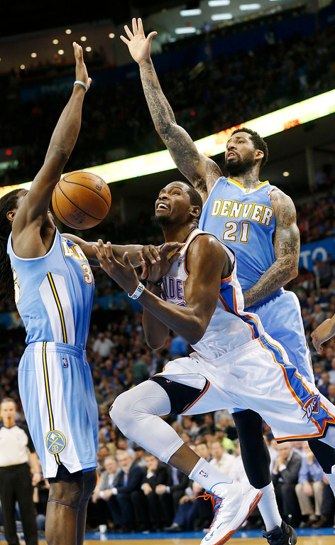 . Oklahoma City Thunder forward Kevin Durant (35) is fouled as he drives between Denver Nuggets forward Kenneth Faried (35) and forward Wilson Chandler (21) in the fourth quarter of an NBA basketball game in Oklahoma City, Tuesday, March 19, 2013. Denver won 114-104. (AP Photo/Sue Ogrocki)