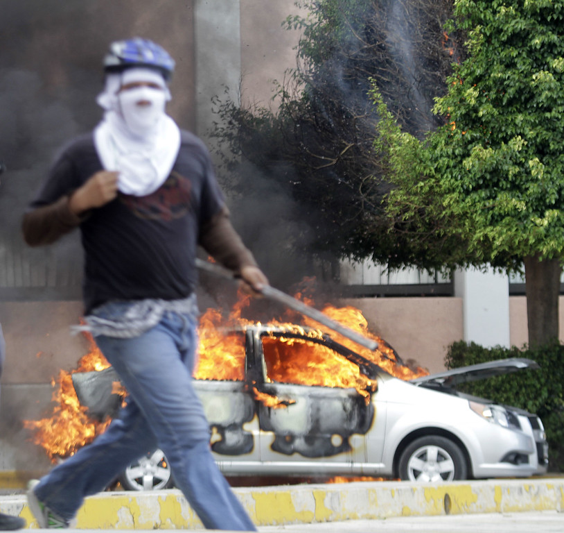 . A protester is seen in front of a car set ablaze in Chilpancingo, Guerrero State, Mexico on November 12, 2014. Pedro PARDO/AFP/Getty Images