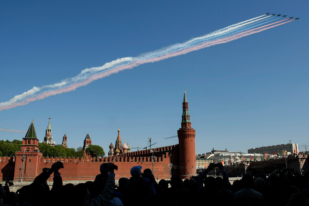 . People take pictures of Russian army jets streaking the sky with colors of a Russian flag during the Victory Day parade in Moscow, Russia, Friday, May 9, 2014. (AP Photo/Denis Tyrin)