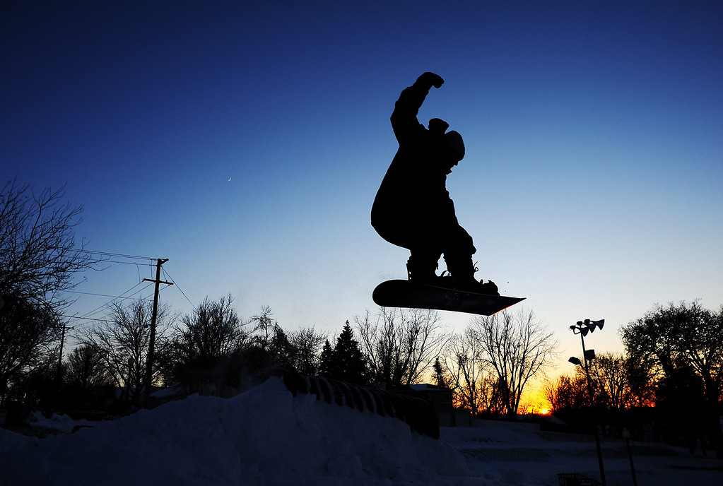 . Despite cold temperatures, Tyler Kremer, 19, of Sioux Falls, catches some air while snowboarding at Terrace Park in Sioux Falls, S.D. as the sun sets in the background on Thursday evening, Dec. 5, 2013.  Winter storm and ice warnings are in effect through much of today for parts of six states in the Midwest. (AP Photo/Argus Leader, Joe Ahlquist)