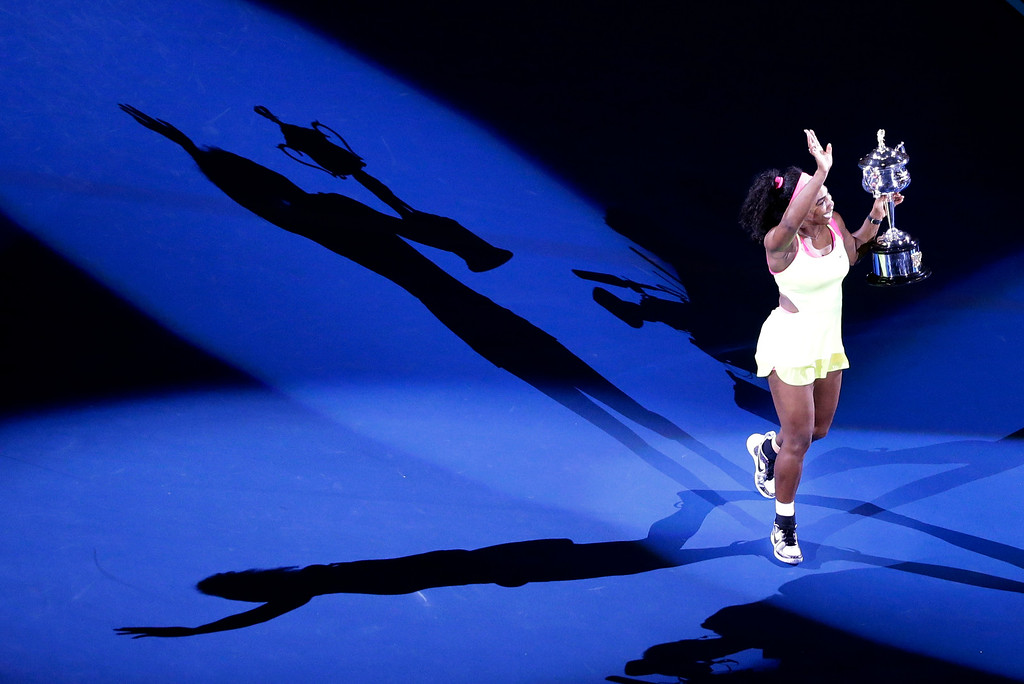 . Serena Williams of the U.S., holding the trophy, casts a shadow on the court,  after defeating Maria Sharapova of Russia in during their women\'s singles final at the Australian Open tennis championship in Melbourne, Australia, Saturday, Jan. 31, 2015. (AP Photo/Lee Jin-man)