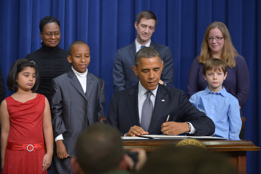 . US President Barack Obama signs executive actions to curb gun violence as invited guests look on January 16, 2013 in the South Court Auditorium of the Eisenhower Executive Office Building, next to the White House in Washington, DC. President Obama Wednesday signed 23 executive actions to curb gun violence and demand Congress pass an assault weapons ban and other sweeping measures in response to the Newtown massacre. A senior official also said Obama would call on Congress to pass deeper measures, including bans on high-capacity magazine clips of more than 10 rounds and to prohibit armor-piercing bullets. AFP PHOTO/Mandel  NGAN/AFP/Getty Images