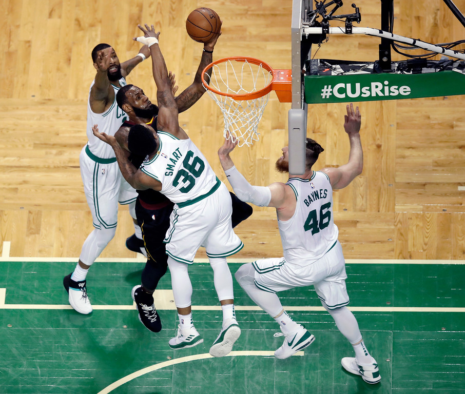 . Cleveland Cavaliers forward LeBron James, center, drives between Boston Celtics forward Marcus Morris, left, and Boston Celtics guard Marcus Smart (36) during the first half in Game 7 of the NBA basketball Eastern Conference finals, Sunday, May 27, 2018, in Boston. (AP Photo/Charles Krupa)