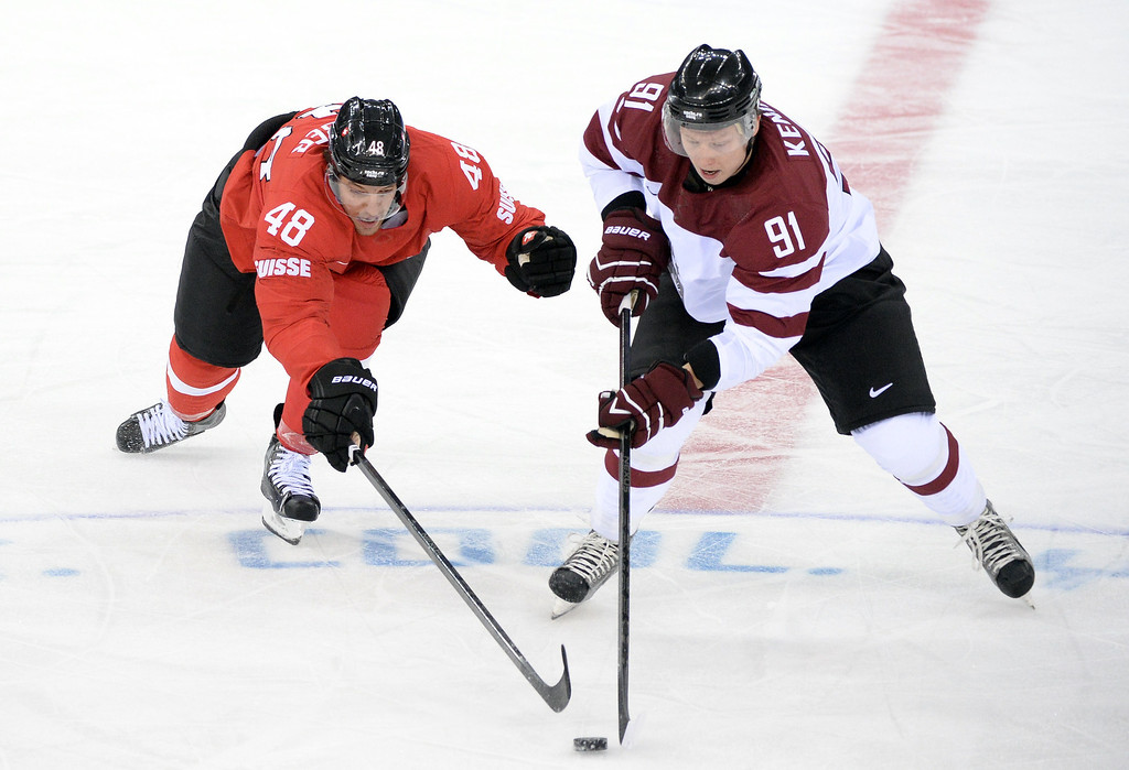 . Switzerland\'s Matthias Bieber (L) vies with Latvia\'s Ronalds Kenins during the Men\'s Ice Hockey match between Latvia and Switzerland at the Shayba arena during the Sochi Winter Olympics on February 12, 2014. ANDREJ ISAKOVIC/AFP/Getty Images