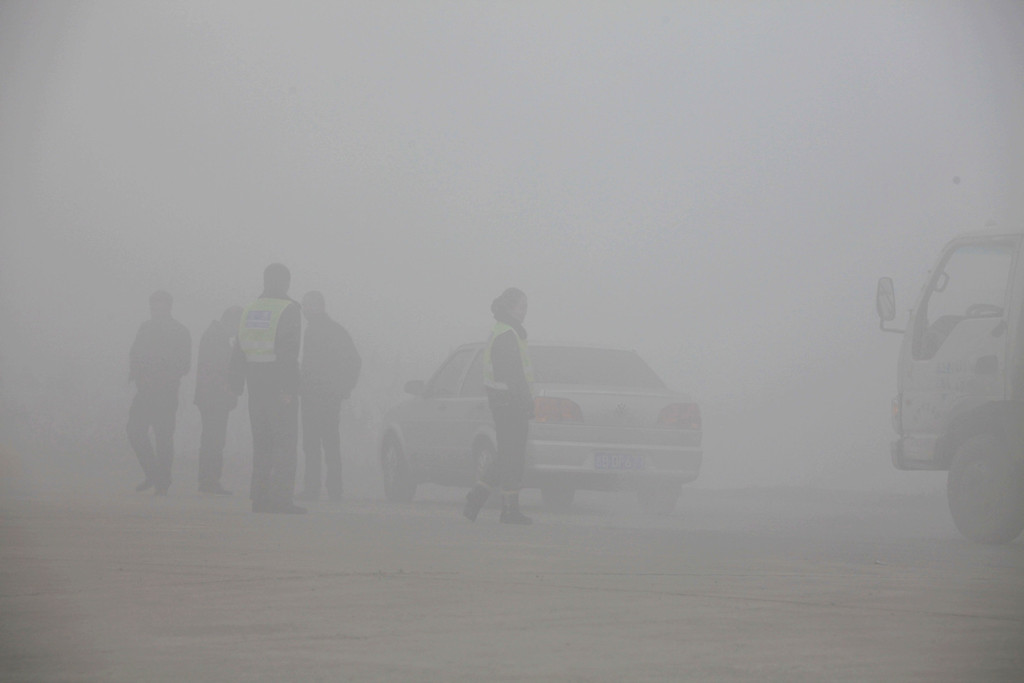 . Traffic police are seen at a toll booth on a highway as vehicles are forced to wait due to heavy smog in Jilin, northeast China\'s Jilin province on October 22, 2013.     AFP PHOTOSTR/AFP/Getty Images