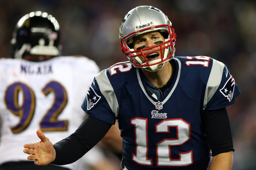 Description of . Tom Brady #12 of the New England Patriots reacts after a play against the Baltimore Ravens during the 2013 AFC Championship game at Gillette Stadium on January 20, 2013 in Foxboro, Massachusetts.  (Photo by Elsa/Getty Images)