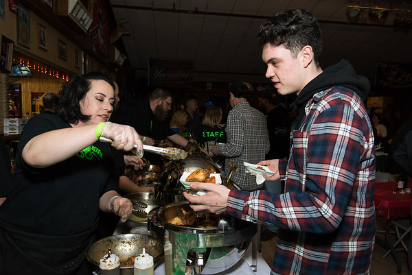 11/05/18 Wesley Bunnell | Staff The Southington Chamber of Commerce held their 13th annual Wing Fest on Monday evening at The Cadillac Ranch in Southington. Carole Fazzina serves Mathieu Hebert at the Groggy Frog table.