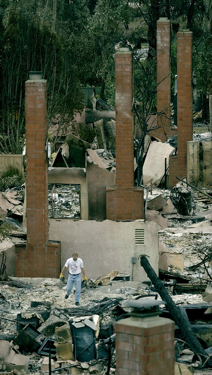 . Markus Weber sorts through rubble at a friend\'s home in the Scripps Ranch area of San Diego, Calif., Thursday, Oct. 30, 2003. The home was among more than 1,400 lost in the Cedar Fire. (AP Photo/Charlie Riedel)