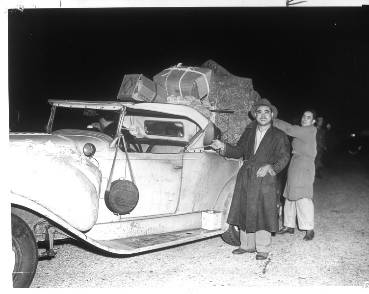 """""""Personal possessions of Jap evacuee are piled high on roadster, one of 300 cars in Manzanar caravan.  Army jeeps, each bearing two soldiers, were escorts.""""--caption on photograph"""