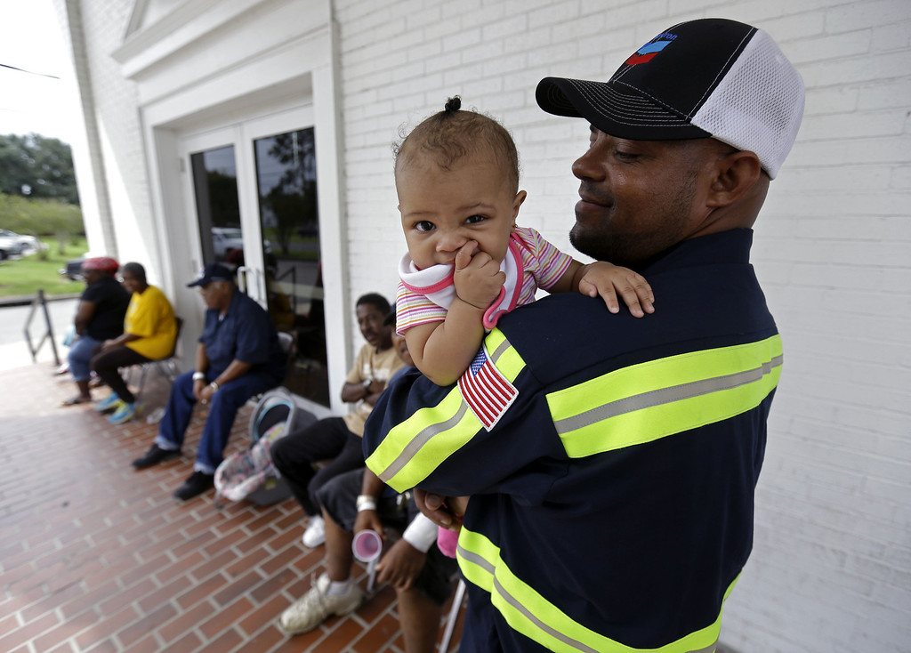 . Gregory Ragas, of Davant, La., holds his daughter Jasmine Ragas, 1 year, at an evacuation shelter in Belle Chasse, La., in anticipation of Tropical Storm Karen, Saturday, Oct. 5, 2013. The East Bank of Plaquemines Parish has been under a mandatory evacuation, which has been downgraded to a voluntary evacuation.  in Belle Chasse, La., Saturday, Oct. 5, 2013. (AP Photo/Gerald Herbert)