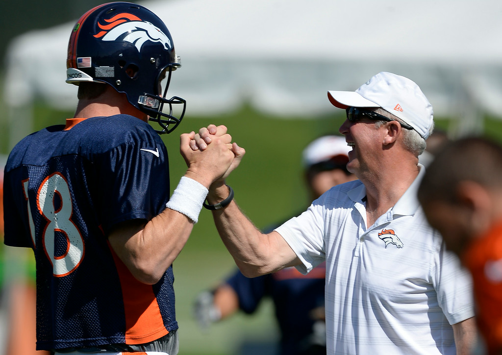 . Denver Broncos quarterback Peyton Manning (18) get high five from Denver Broncos head coach John Fox before he start of practice at the  2014 training camp August 11, 2014 at Dove Valley. (Photo by John Leyba/The Denver Post)