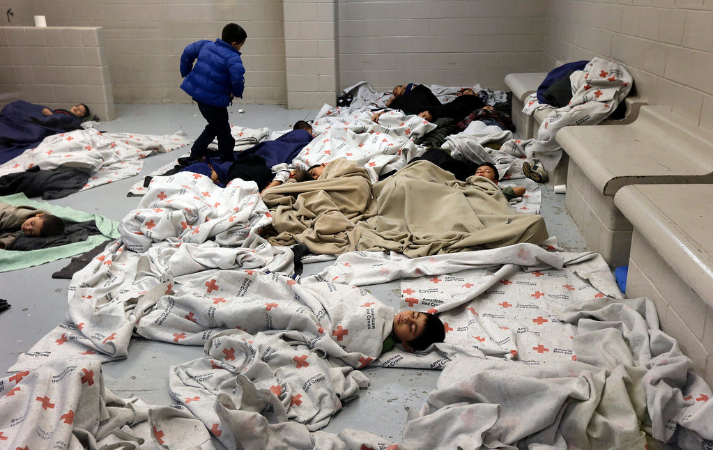 . Detainees sleep in a holding cell at a U.S. Customs and Border Protection processing facility, Wednesday, June 18, 2014, in Brownsville,Texas.   (AP Photo/Eric Gay, Pool)