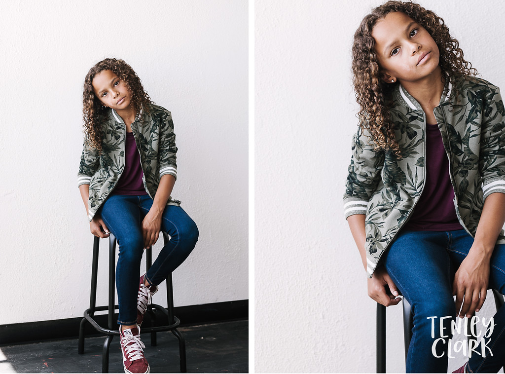 Playful, colorful studio kids headshots by Tenley Clark Photography. Girl white wall in jean and camo look.