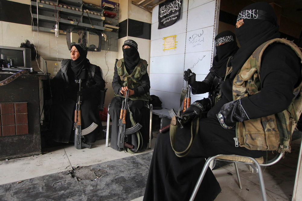 . Women members of the Al-Ikhlas (Loyalty) Battalion rest with their weapons in Aleppo March 31, 2013. The Al-Ikhlas (Loyalty) Battalion is a security battalion that involves women that are in charge of erecting sudden checkpoints and raiding houses that contain women in Aleppo. The battalion is under the Ghorabaa (Strangers) Al-Sham Front, controlled by the Free Syrian Army.   REUTERS/Giath Taha
