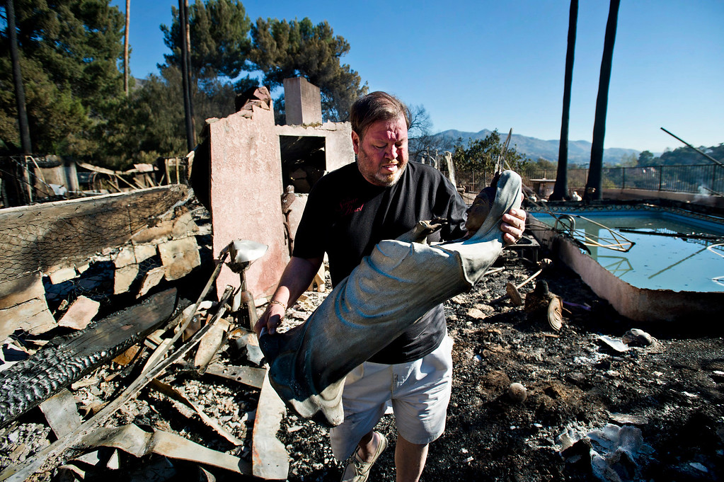 . Greg Peterson saves an antique religious statue from the remains of his home after it was destroyed by the Colby Fire in Glendora on Friday morning, Jan. 17, 2014. Glendora residents return to their homes this morning after the mandatory evacuations were lifted. (Photo by Watchara Phomicinda/ San Gabriel Valley Tribune)
