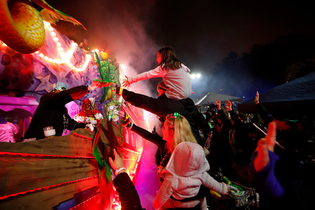 . Float riders hand beads to the crowd as the Krewe of Orpheus rolls in New Orleans, Monday, Feb. 12, 2018. (AP Photo/Gerald Herbert)