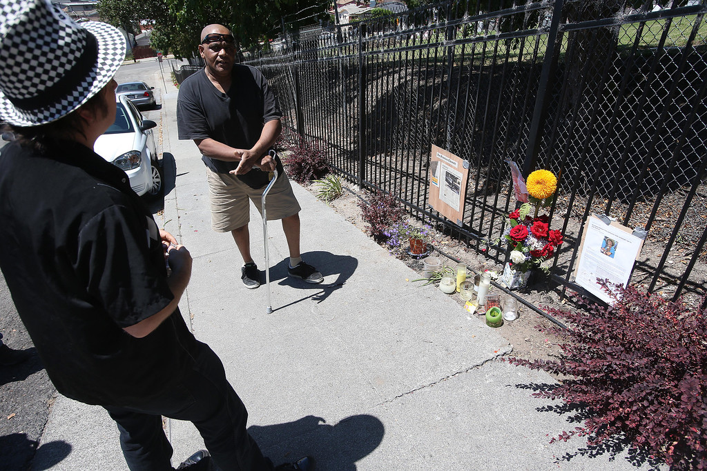 . Neighborhood residents Darrele Tyler, center, and Mike Martzke, left, visit a memorial for homicide victim Judy Salamon on Fern Street in Oakland, Calif., on Thursday, July 25, 2013. Salamon, 66, was shot and killed Wednesday afternoon while driving a few blocks from her home in Oakland\'s Fairfax district, marking the city\'s 56th homicide of the year. (Jane Tyska/Bay Area News Group)