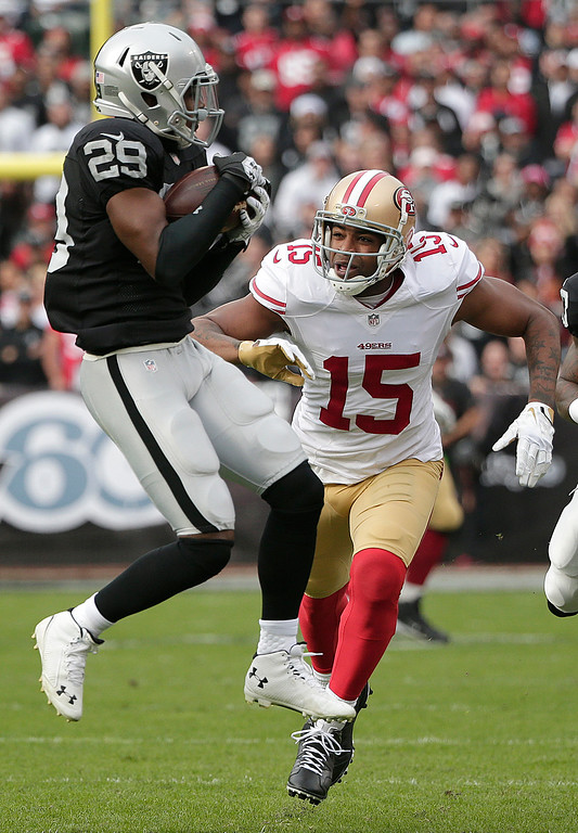 . Oakland Raiders cornerback Brandian Ross (29) intercepts a pass intended for San Francisco 49ers wide receiver Michael Crabtree (15) during the first quarter of an NFL football game in Oakland, Calif., Sunday, Dec. 7, 2014. (AP Photo/Marcio Jose Sanchez)