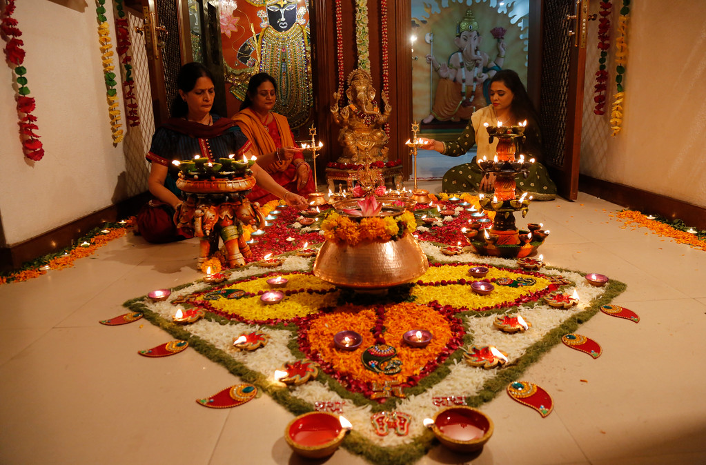 . Members of an Indian Hindu family light earthen lamps on a rangoli, a hand decorated pattern on the floor, as part of Diwali festivities in Ahmadabad, India, Thursday, Oct. 19, 2017. Diwali, the festival of lights, is being celebrated across the country Thursday. (AP Photo/Ajit Solanki)