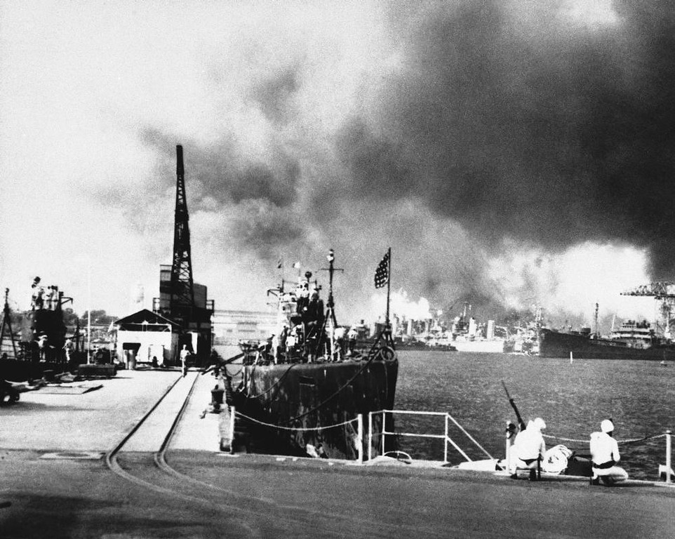 . Smoke clouds the sky over Pearl Harbor as two sailors crouch with their rifles on a pier at the submarine base, trying desperately to locate an enemy to fire upon, Dec. 7, 1941. Submarines berthed nearby are USS Tautog and USS Narwhal. (AP Photo)