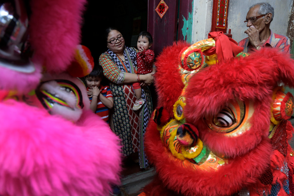. An Indian man, right, looks on as an ethnic Chinese woman and her children watch a lion dance procession on the first day of Chinese lunar new year in Kolkata, India, Friday, Feb. 16, 2018. People in Asia and around the world are celebrating the Lunar New Year on Friday with festivals, parades and temple visits to ask for blessings. This year marks the year of the dog, one of the 12 animals in the Chinese astrological chart. (AP Photo/Bikas Das)