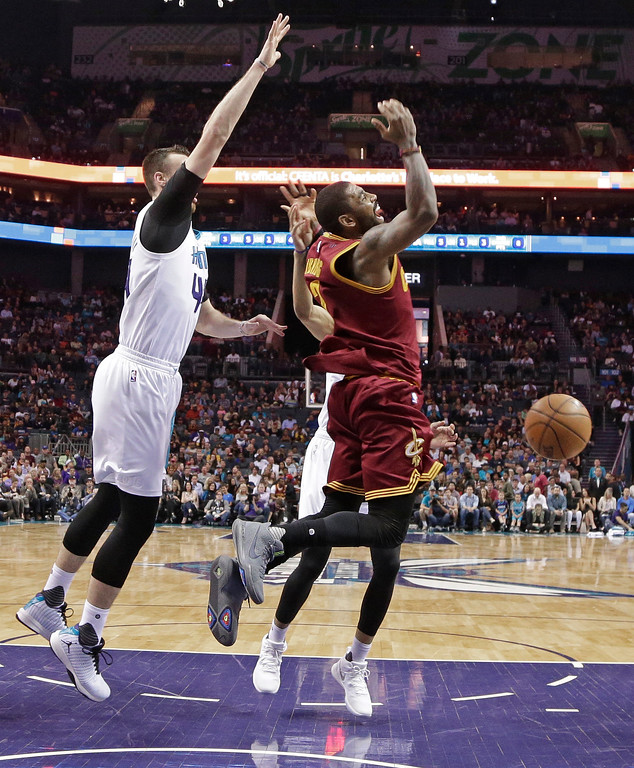 . Cleveland Cavaliers\' Kyrie Irving, right, reacts to a foul as he drives past Charlotte Hornets\' Frank Kaminsky, left, during the first half of an NBA basketball game in Charlotte, N.C., Friday, March 24, 2017. (AP Photo/Chuck Burton)